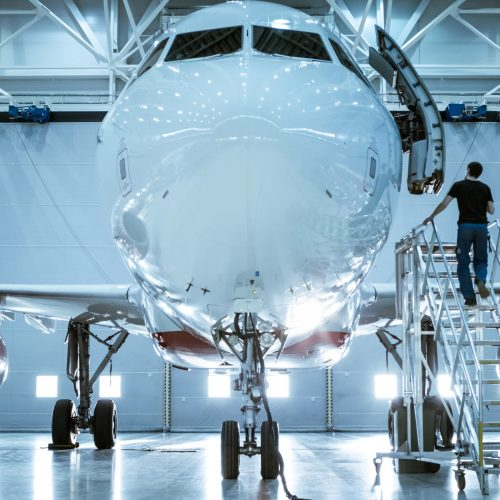 Brand New Airplane Standing in a Aircraft Maintenance Hangar while Aircraft Maintenance Engineer/ Technician/ Mechanic goes inside Cabin via Ladder/ Ramp.
